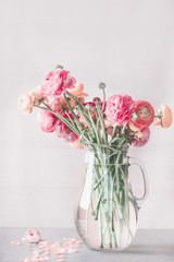 Pastel color ranunculus flowers bunch in glass vase on table, front view