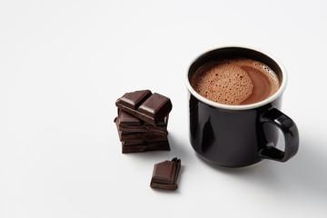 Black mug with hot chocolate served with chunks of dark chocolate