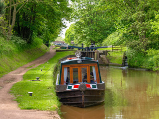 Moored narrowboat between two canal locks  on the Shropshire Union Canal near Audlem in Cheshire, England.