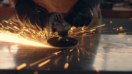 Worker using industrial grinder. Worker in garage makes work with metall and grinder.