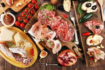Italian antipasti wine snacks set. Cheese variety, Mediterranean olives, pickles, Prosciutto di Parma and salami