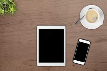 Brown wooden office desk top view with smartphone, tablet pc, plant and cup of coffee