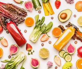 Red and yellow smoothie bottles with organic fruits and vegetables ingredients on white desk background, top view, flat lay. Healthy clean and detox, weight loss dieting or fasting  food concept