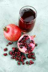 Glass of pomegranate juice and pomegranate fruit on old background