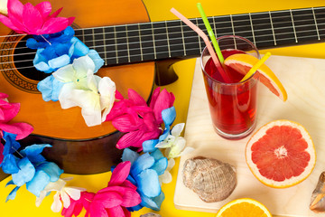 Hawaiian party concept: handmade DIY lei from faux flowers, alcohol-free fresh red drink and juicy fruits - orange and grapefruit, sea shells, vacation concept, flat lay on yellow background