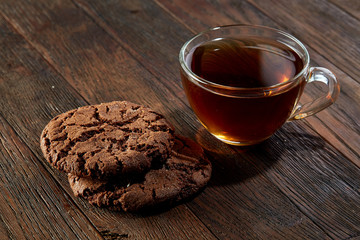 Cup of tea with cookies on a cutting board on a wooden background, top view