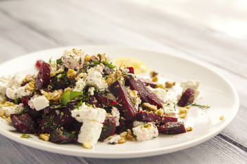 Beetroot salad with cottage cheese and walnuts. European cuisine. Top view. Vegan dish. Vegetarian appetizer. Simple side dish. Toned photo.