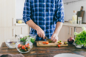 Man cooking summer salad of vegetables on wooden table in home kitchen