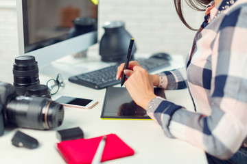 pretty young woman photographer with camera in office