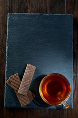 Cup of tea with meringues on a wooden background, top view