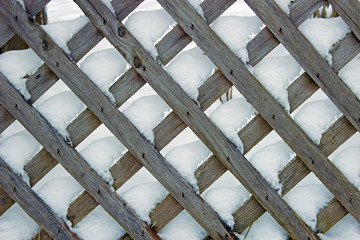 Snow coated latticework fence for background or wallpaper