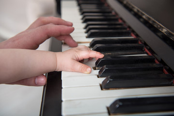 Dad helps the child play the piano