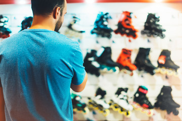 Assortment roller skates isolated in store shop, person choosing and buy color roller-skates on backgraund sun flare, healthy and activity lifestyle concept close up, man consider sport footwear