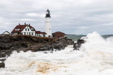 Portland Head Lighthouse during a storm with large waves.
