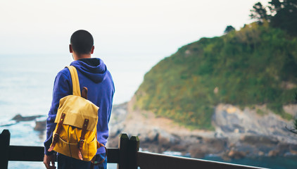 traveler relax holiday concept, guy enjoying ocean horizon, sunlight view in trip vacation, hipster hiker tourist with backpack looking on seascape sunset, background blue sea and mountain