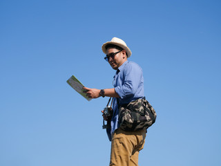 Asian man travel with map and vintage camera on blue sky background