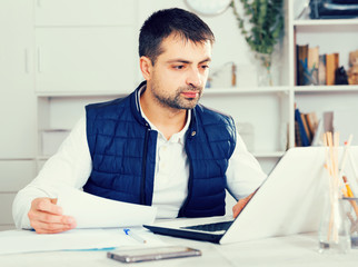Businessman in shirt working with laptopt and documents