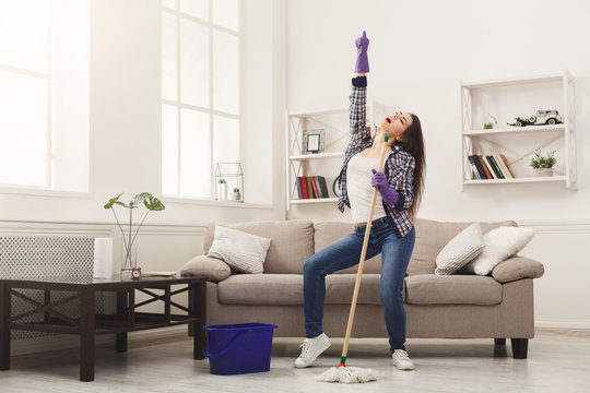 Happy woman cleaning home with mop and having fun