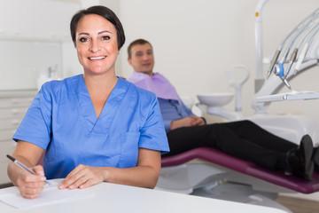 dentist in uniform writing document