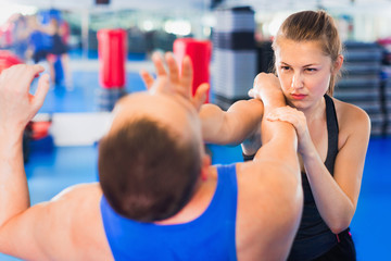 Woman is training with man on the self-defense course in gym.