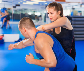 Woman is training captures with man on the self-defense course in gym.