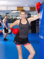 Portrait of young active woman  with punching bag
