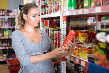 Future mother is reading structure of product on shelves