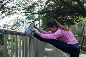 Fitness sport girl fashion sportswear doing yoga fitness exercise in street. Fit young asian woman doing training workout in morning. Young happy asian woman stretching at park after running workout.