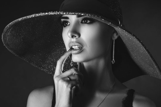 beautiful portrait of a girl in a hat on a black background, black and white photo