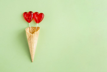 Composition of red heart-shaped lollipops in waffle Cup on green background