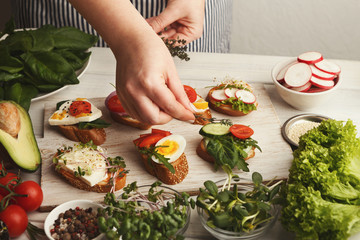 Feamale hands making healthy bruschettas for right snack