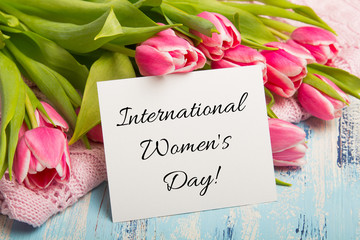 International Women's Day card Pink tulip bouquet and balnk paper on blue wooden background. Beautiful flowers
