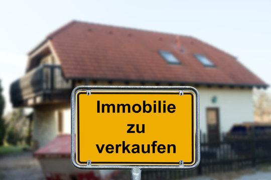 Verkauf / Eigenheim und Ortsschild mit den Worten Immobilie zu verkaufen