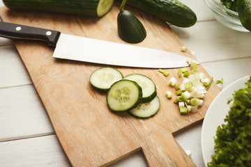 Cutting cucumber for fresh salad top view