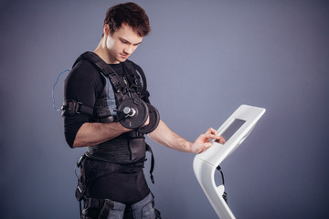 man in Electrical Muscular Stimulation suit standing with dumbbells near ems tablet and push on screen