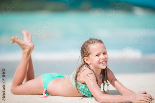 b6a1ce1745595 Adorable little girl lying in shallow water on white beach