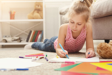 Smiling little girl drawing with colored pencils at home