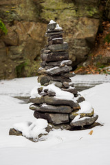 Stones on wintry river covered snows. Winter landscape.  Stack of pebble stones on snow.