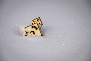 Small toy wooden house swept by snow