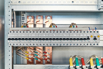 Modular electrical circuit breakers and differential switches in electrical Cabinet. Electrical wires connected to the breakers and copper bus bars. Electrical equipment on the mounting panel.