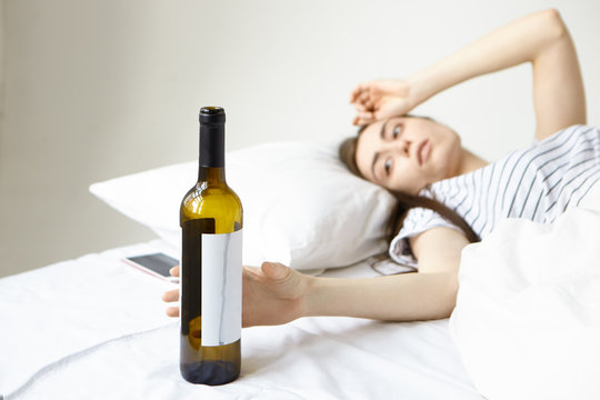 Alcoholism and booze. Stressed female in bed suffering from terrible headache after alco party with friends last night, reaching for glass bottle of wine, hoping to ease hangover. Film effect