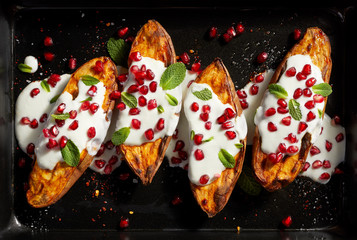Baked sweet potatoes with garlic mint yogurt sauce sprinkled with pomegranate seeds and fresh mint leaves on a black background . Delicious and healthy vegetarian meal