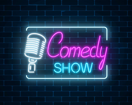 Neon sign of comedy show with retro microphone symbol on a brick wall background. Humor glowing signboard.