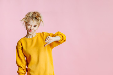 close-up portrait of cheerful  young caucasian female with curly blonde hair, in yellow sweater poses on a pink background. woman making thumb down, dissatisfied and angry.