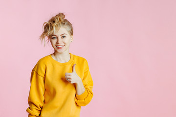 close-up portrait of cheerful  young caucasian female with curly blonde hair, in yellow sweater poses on a pink background. woman making thumb up sign and smiling cheerfully.