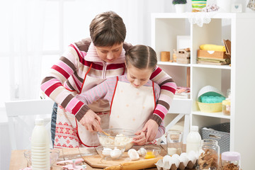 Mother and daughter cook at home. Kitchen interior, healthy food concept