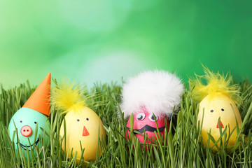 Eggs with funny faces in green grass
