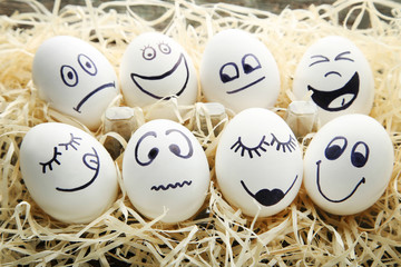 Eggs with funny faces in nest on wooden table