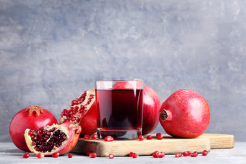 Wall Mural - Pomegranate fruit and juice in glass on grey wooden table