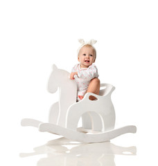 Toddler baby girl is riding swinging on a rocking chair toy horse over white
